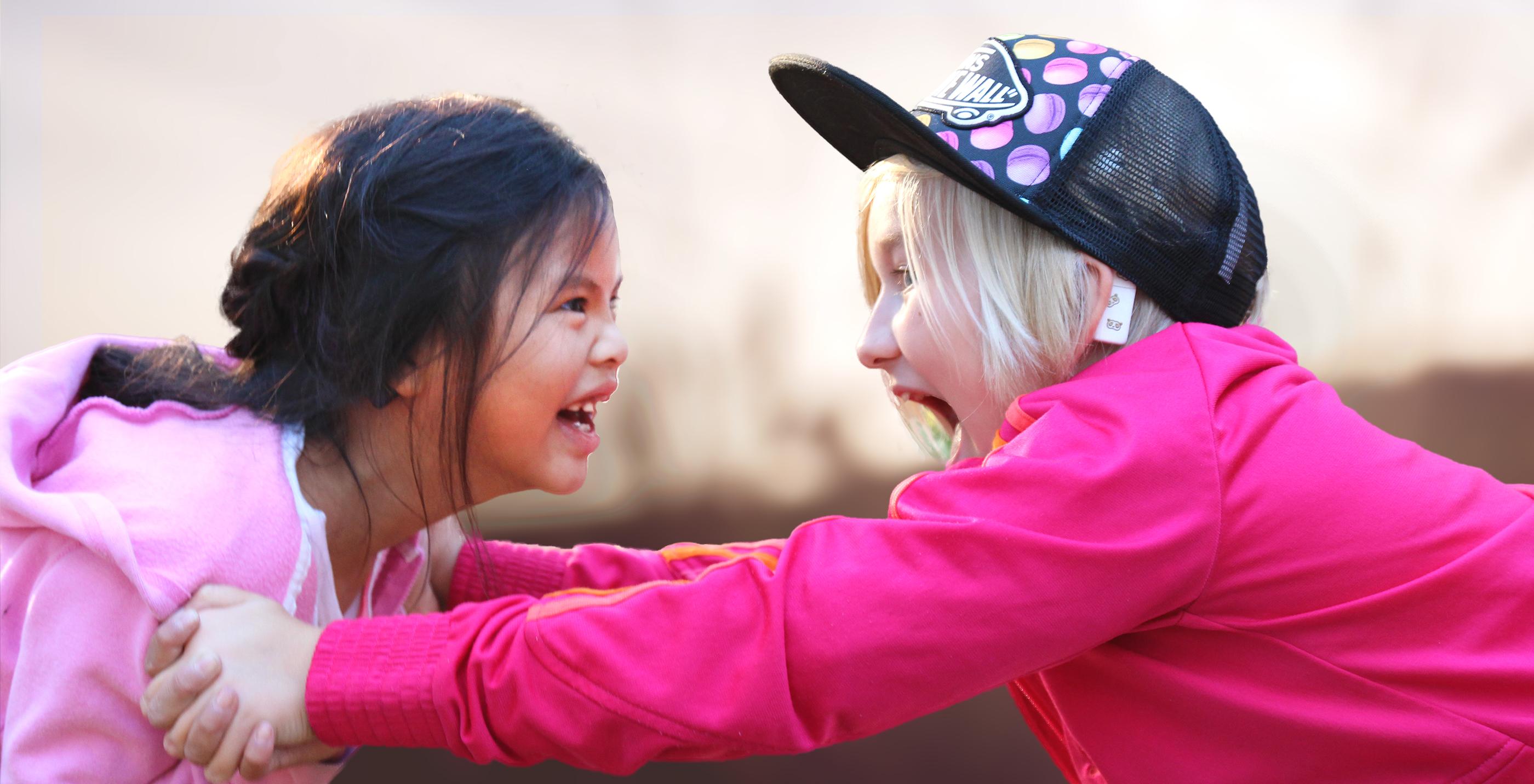 Kuvassa kaksi lasta hymyilee toisilleen