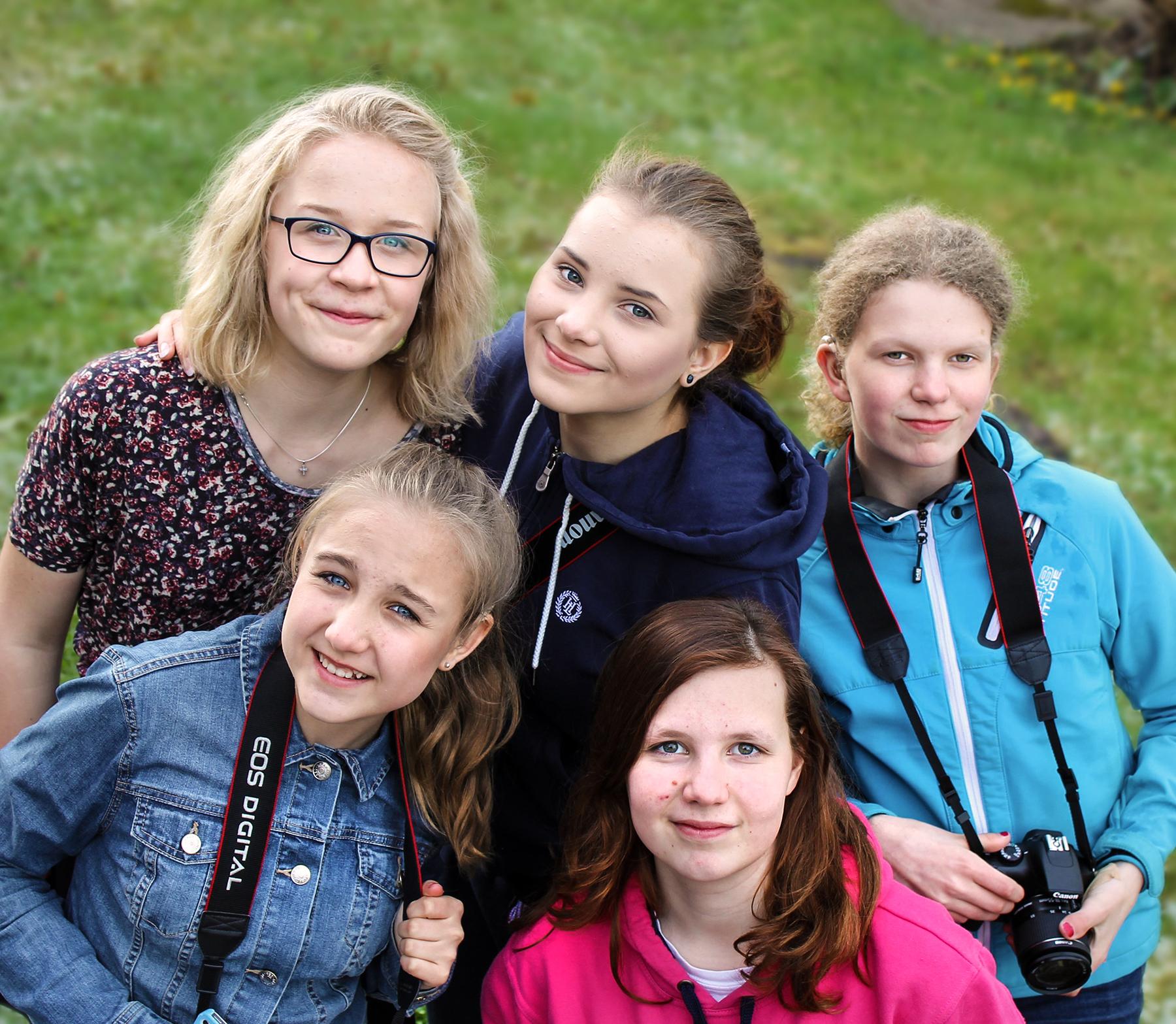 Kuvassa joukko nuoria hymyilee kameralle