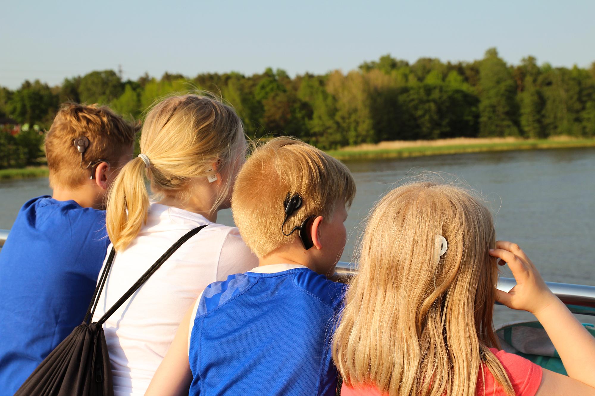 Kuvassa neljä sisäkorvaistutteita käyttävää lasta ja nuorta takaapäin kuvattuina