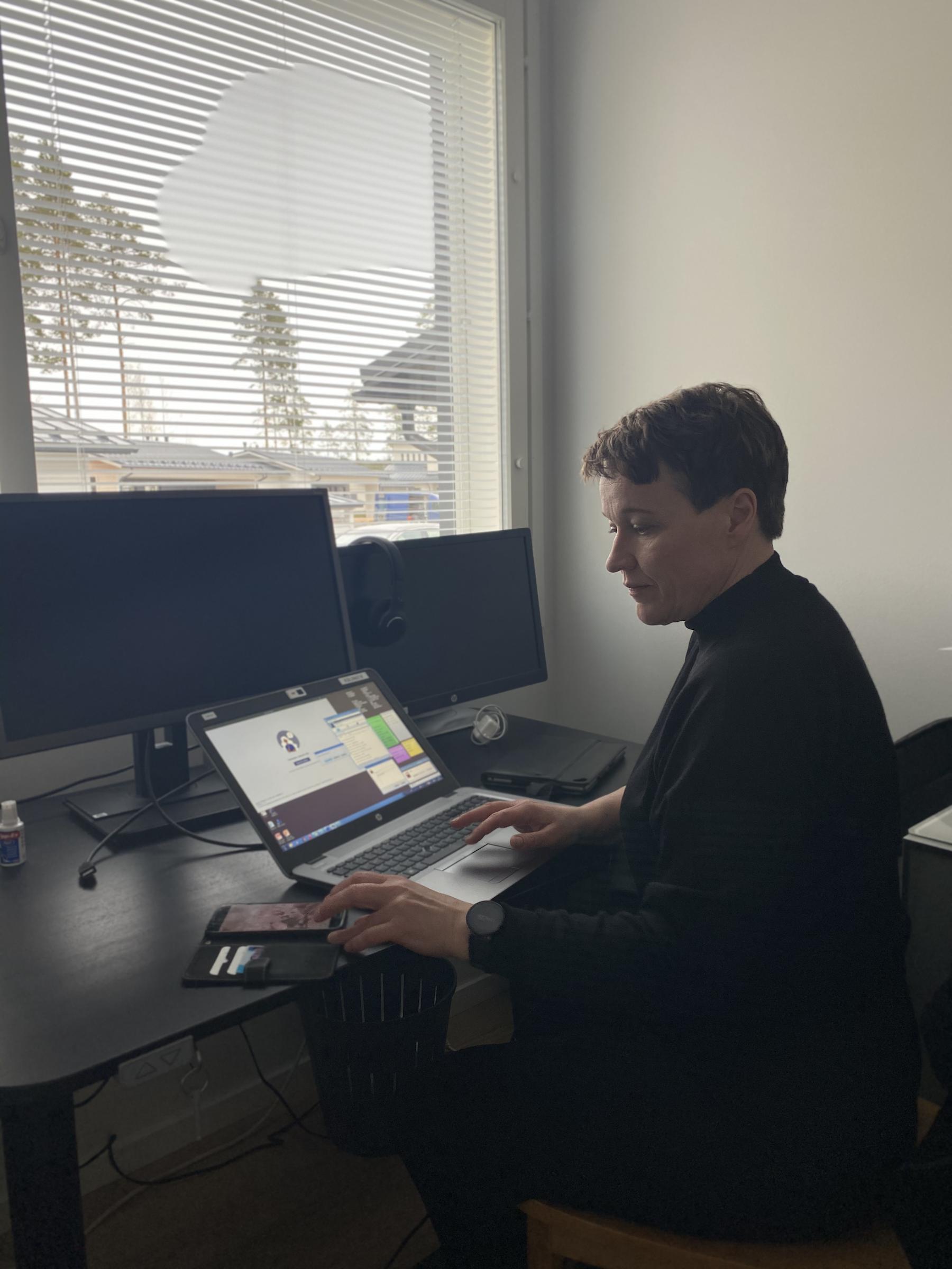 Kuvassa vieraskynän kirjoittaja, kuntoutusohjaaja Laila Paananen tietokoneen ääressä