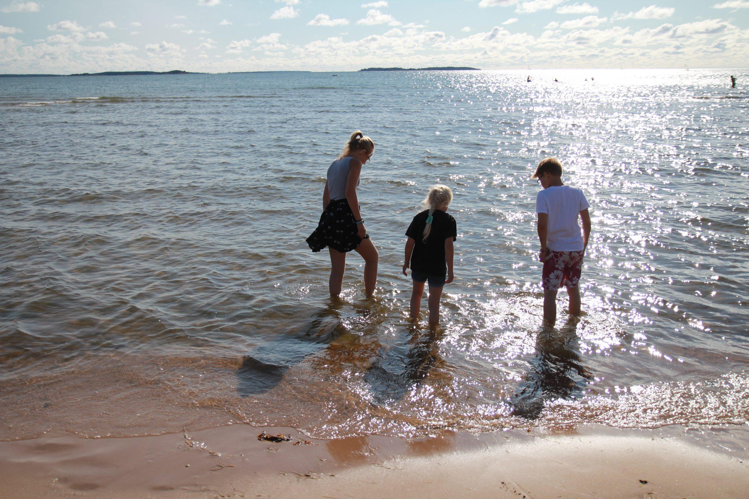 Kuvassa lapsia kahlaamassa rantavedessä