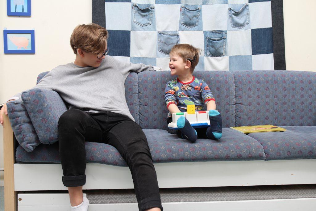 Nuori ja SI-lapsi istuvat sohvalla ja katsovat toisiinsa  / #onneksionjoku -kampanja järjestöjen tukena