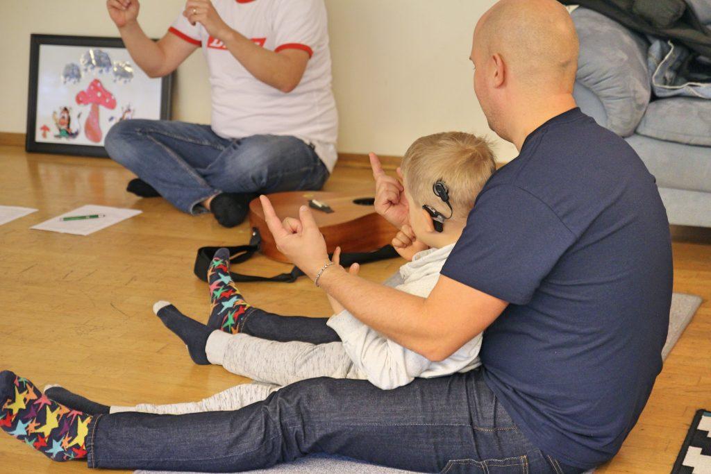 Kuvassa isä lapsi sylissään leikkimässä CIsumusan puhemuskarissa