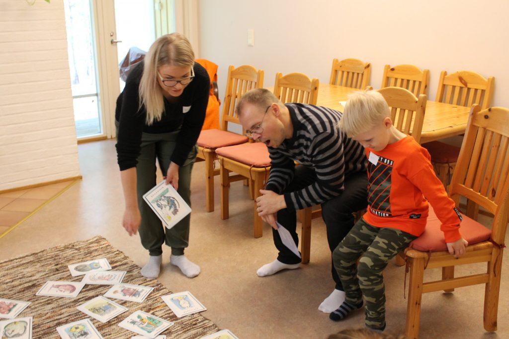 Kuvassa yksi pienten viikonloppuun osallistunut perhe valitsemassa itselleen kortteja