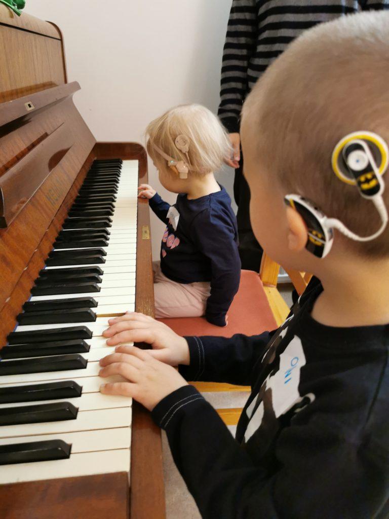 Pieniä imppakäyttäjiä soittamassa pianoa pienten lasten viikonlopussa