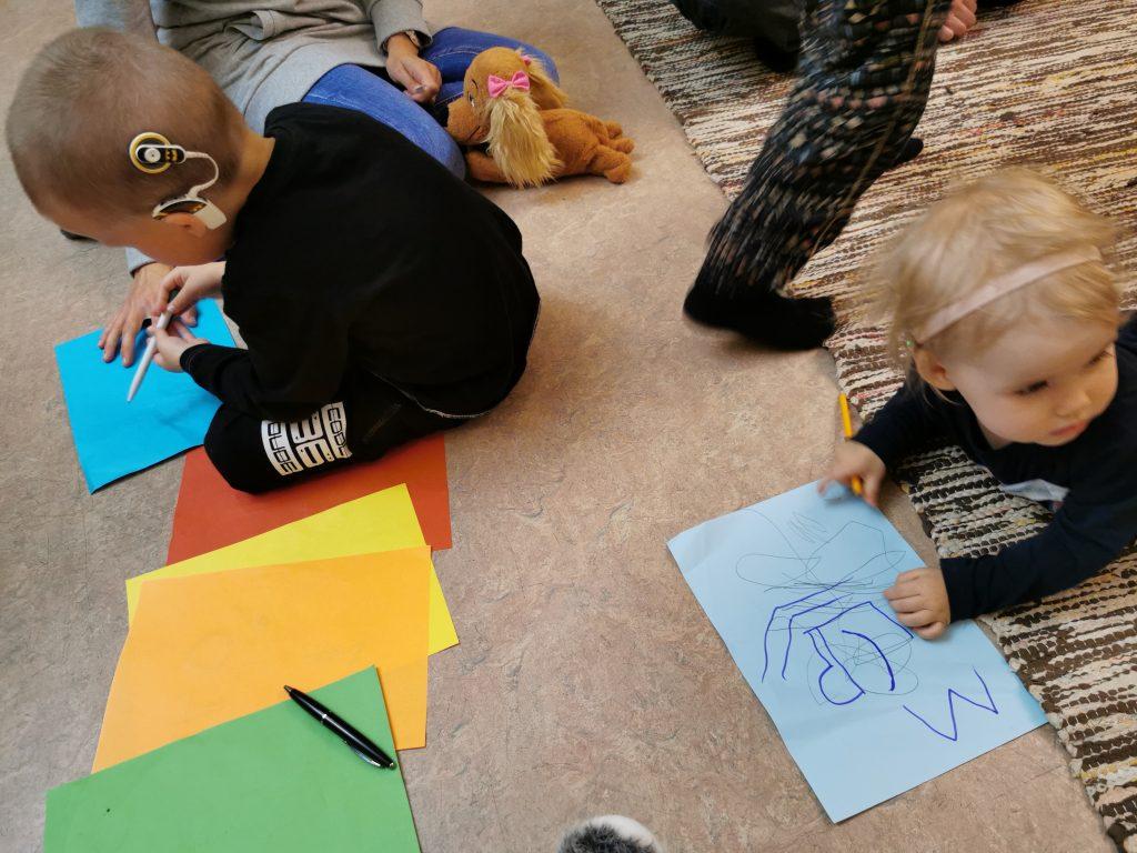 Pieniä SI-käyttäjiä lattialla piirtämässä paperille