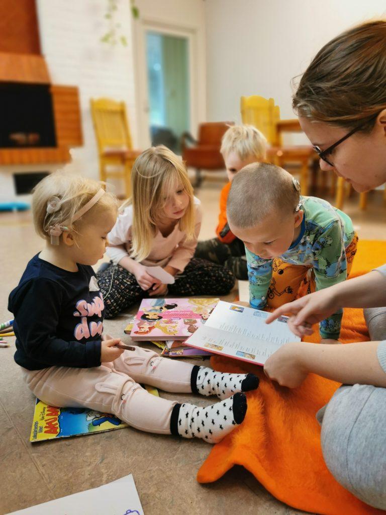 LapCI ry:n työntekijä lukemassa lapsille satua