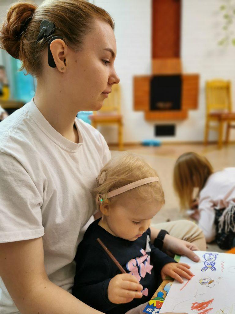 Kuvassa pieni SI-käyttäjä lastenhoitajan sylissä piirtämässä pienten lasten viikonlopussa