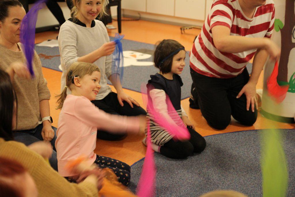 Kuvassa lapsia ja vanhempia ringissä viuhtomassa huiveilla leikin lomassa