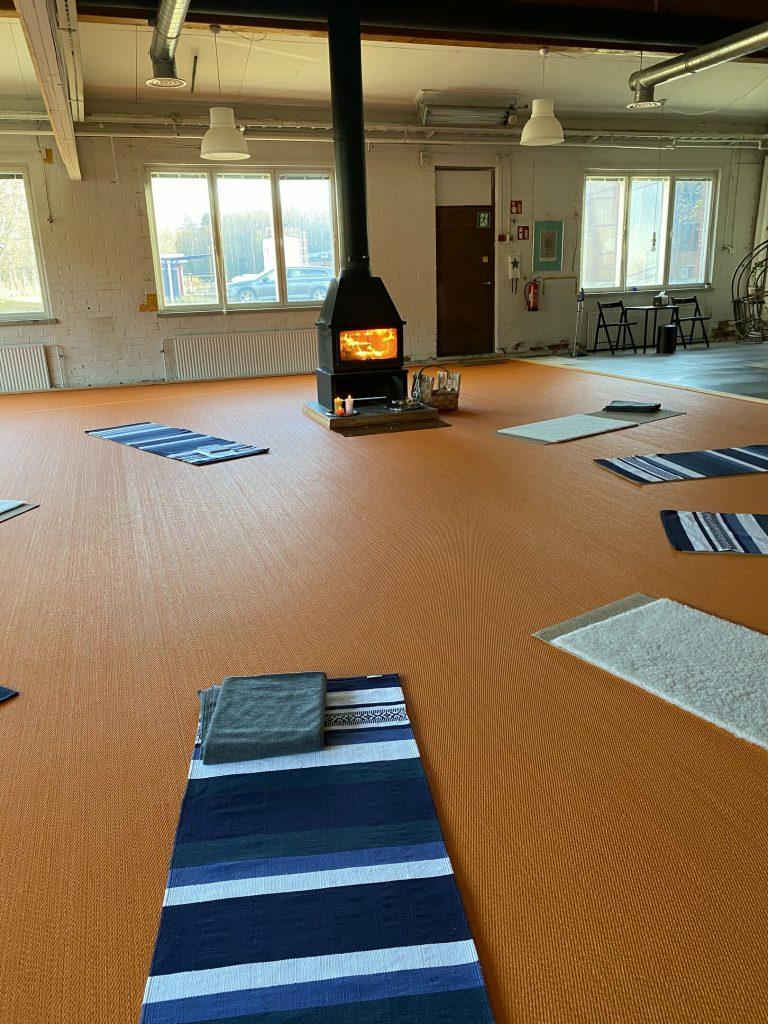 Huone, jonka keskellä on loimuaa takka ja jonka ympärillä on joogamattoja ympyrässä