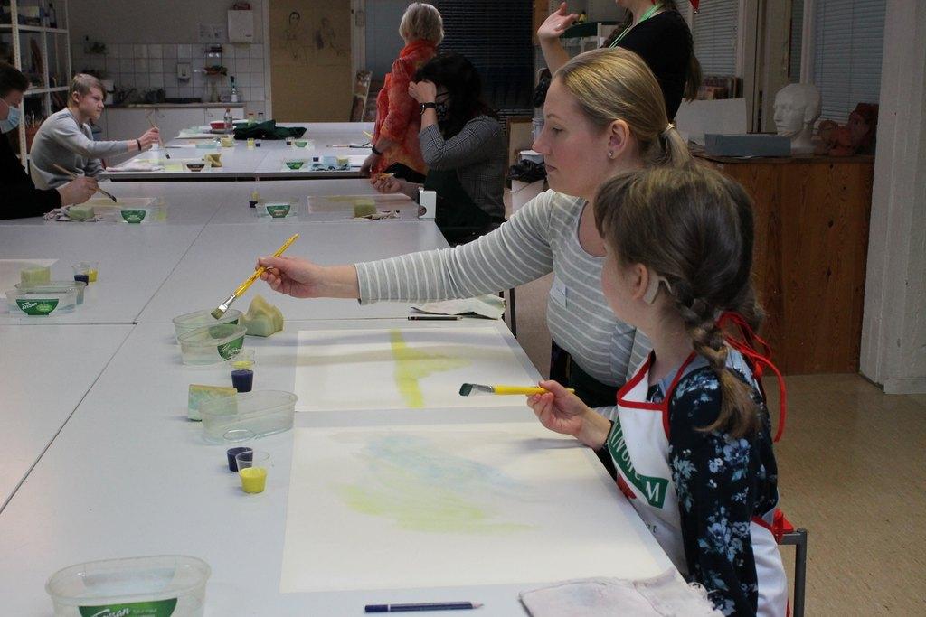 Kuvassa etualalla äiti ja tytär maalaamassa. Takana näkyy pikkujoulujen taidepajan ohjaaja ja muita osallistujia.  / Pikkujoulut