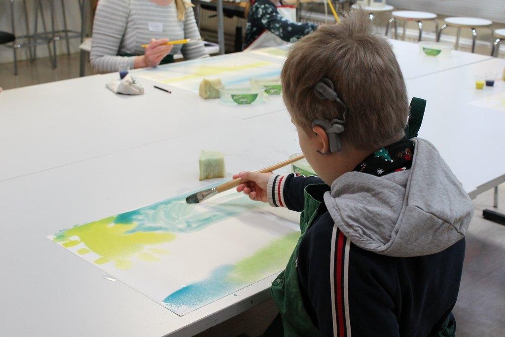 Kuvassa etualalla pikkujouihin osallistunut poika, joka maalaa.