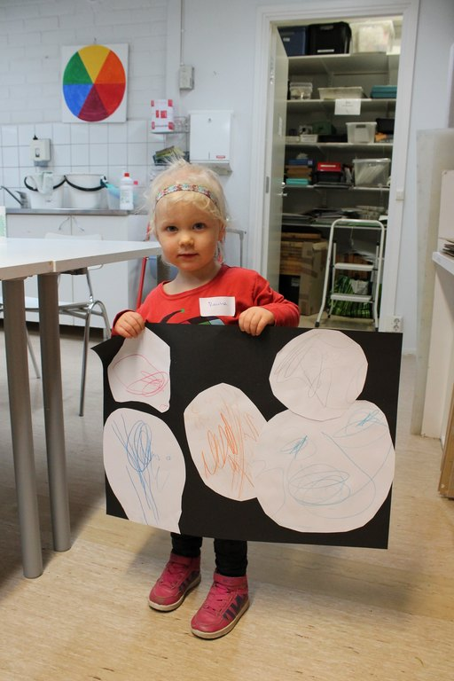 Kuvassa pieni tyttö, joka pitelee isoa kartonkia käsissään. Kartonkiin on liimattu piirustuksia
