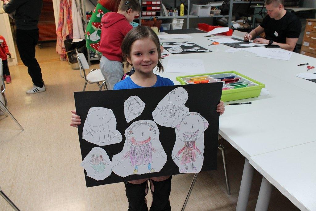Kuvassa etualalla poseeraa pieni tyttö, jolla käsissään kartonki, johon on liimattu hänen piirustuksiaan. Takana näkyy muita osallistujia piirtämässä  / Pikkujoulut