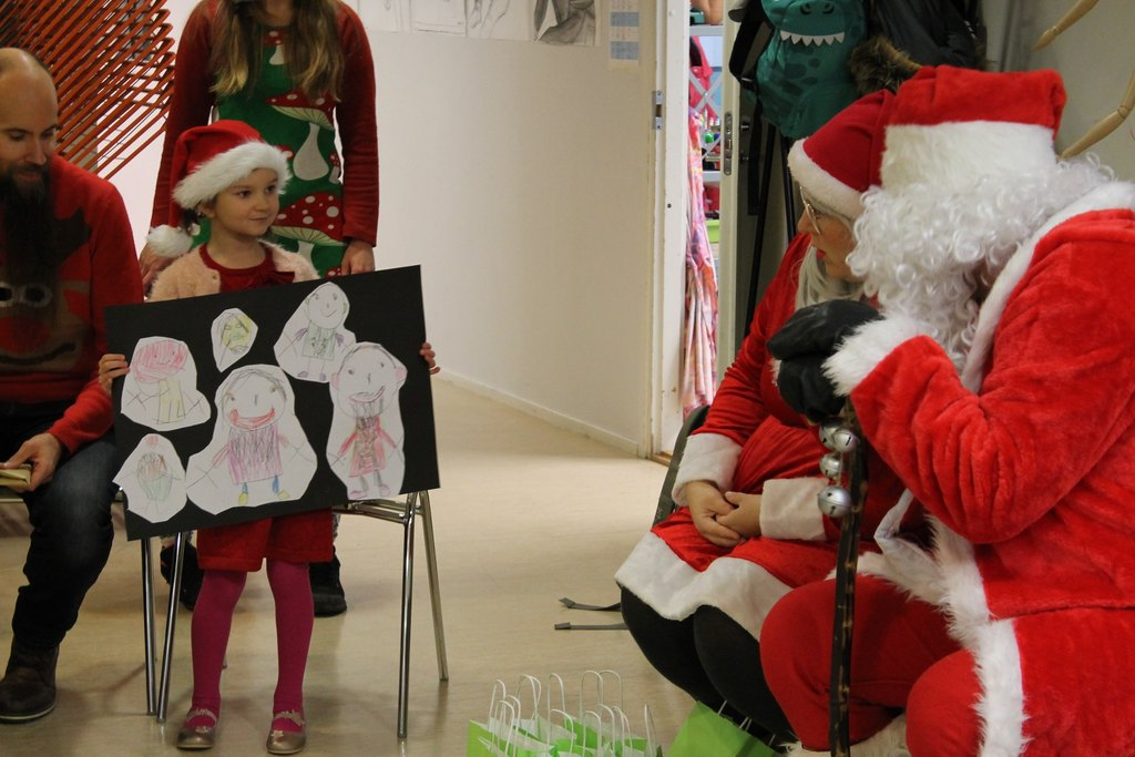 Kuvassa pieni tyttö esittelee tekemäänsä piirroskollaasia joulupukille.   / Pikkujoulut