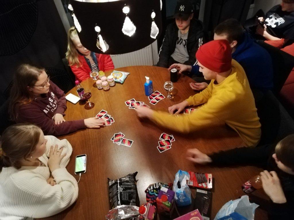 Nuoria (ja ohjaaja) pöydän ääressä pelaamassa Uno-korttipeliä