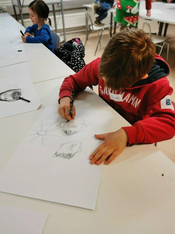 Kuvassa etualalla pieni poika, joka piirtää muotokuvia. Taka-alalla näkyy muita piirustuspajan lapsia.  / Pikkujoulut