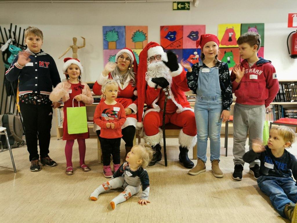 Kuvassa joulupukki, tonttu ja pikkujouluihin osallistuneet lapset ryhmäkuvassa  / Pikkujoulut