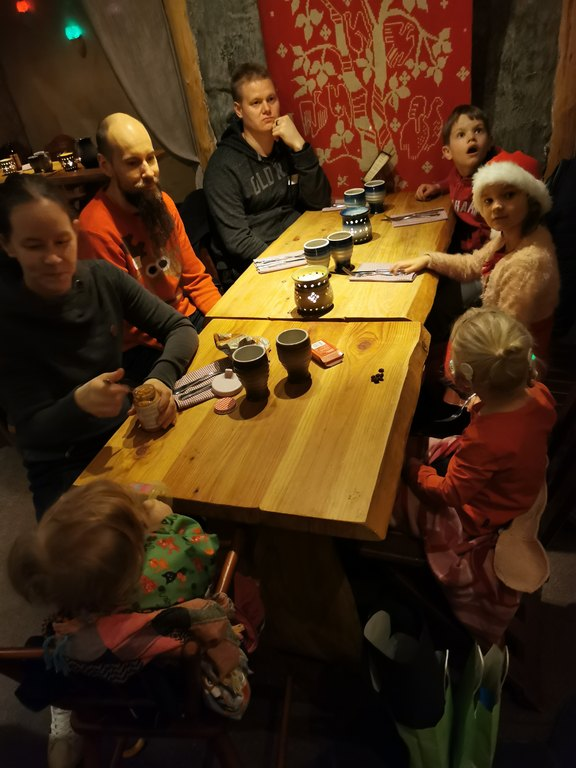 Kuvassa ruokapöydän ääressä vanhempia ja lapsia