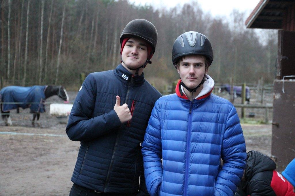 Kuvassa nuorten viikonlopun kaksi osallistujaa, Sten ja Jonathan, poseeraamassa kameralle ratsastuskypärät päässään
