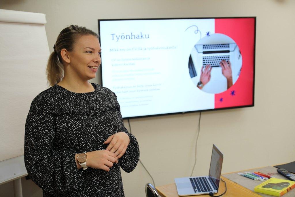 Kuvassa etualalla seisoo ohjaaja Saana, takana näyttö jossa lukee 'Työnhaku'