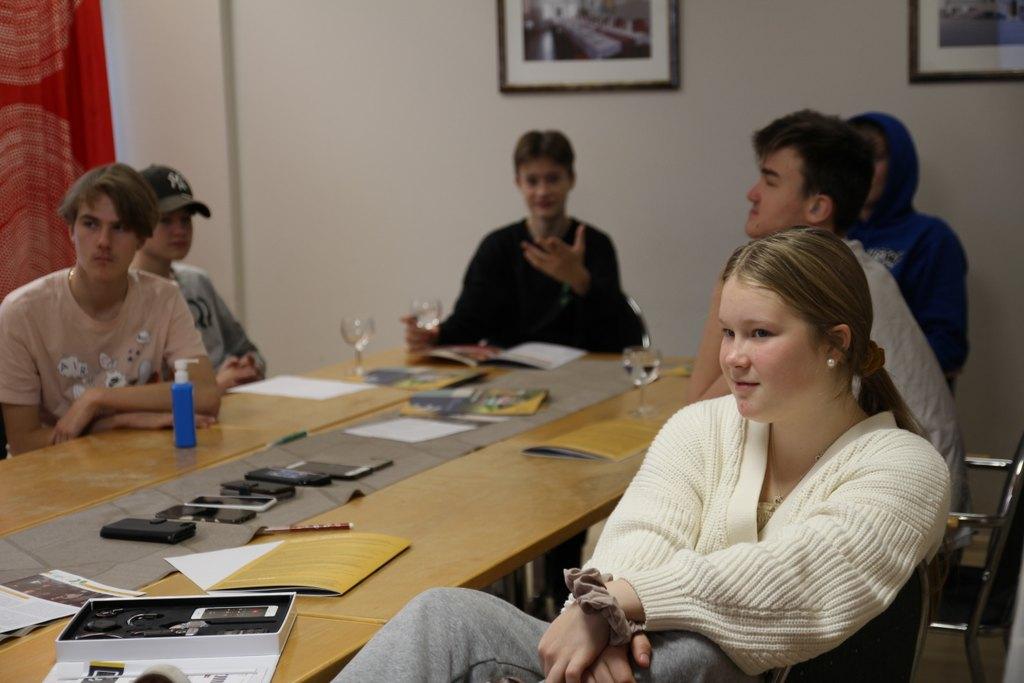Pöydän ääressä nuoria kuuntelemassa luentoa