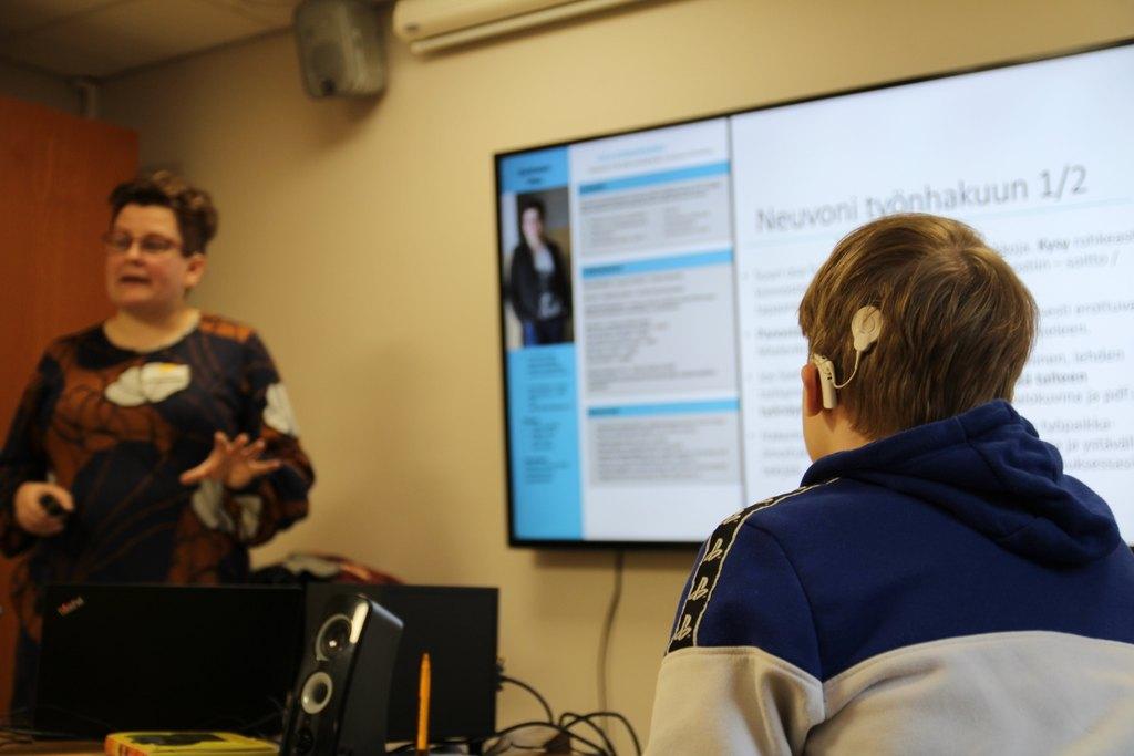 Taka-alalla Ulla Konkarikoski näytön edessä, jossa lukee 'neuvoni työnhakuun'. Etualalla sisäkorvaistutetta käyttävä nuori takaapäin kuvattuna