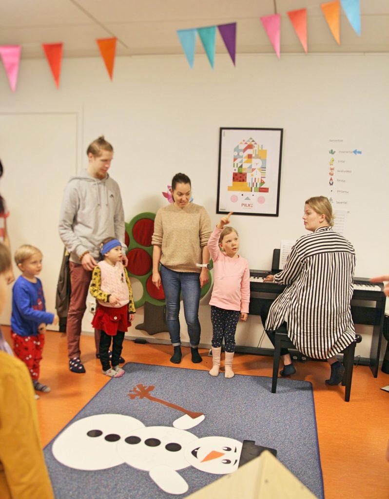 Kuvassa musiikkipedagogiopiskelija Pinja soittamassa pianoa, lapsia ja aikuisia seisoo ringissä ympärillä