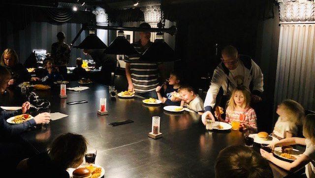 Kuvassa aikuisia ja lapsia ravintolapöydän ääressä syömässä hampurilaisia.