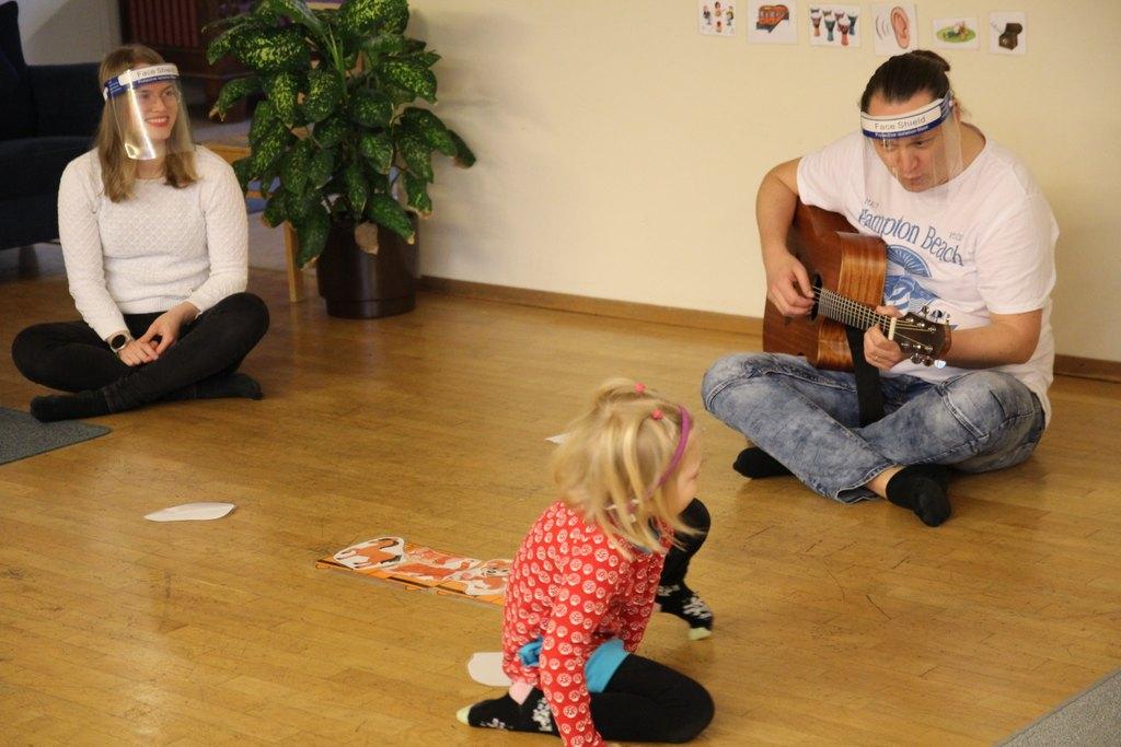 Kuvassa etualalla pieni CIsumulainen (lapsi) ja takana kaksi CIsumusa-ohjaajaa lattialla istumassa, toisella kitara kädessä ja molemmilla visiirit kasvoilla.