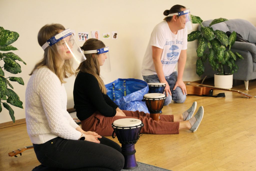 Kuvassa kolme CIsumusan syksyn ohjaajaa lattailla istumassa: kaksi naista etualalla ja yksi mies taaempana. Kaikilla on visiirit päässä ja rumpuja ja kitara edessä.