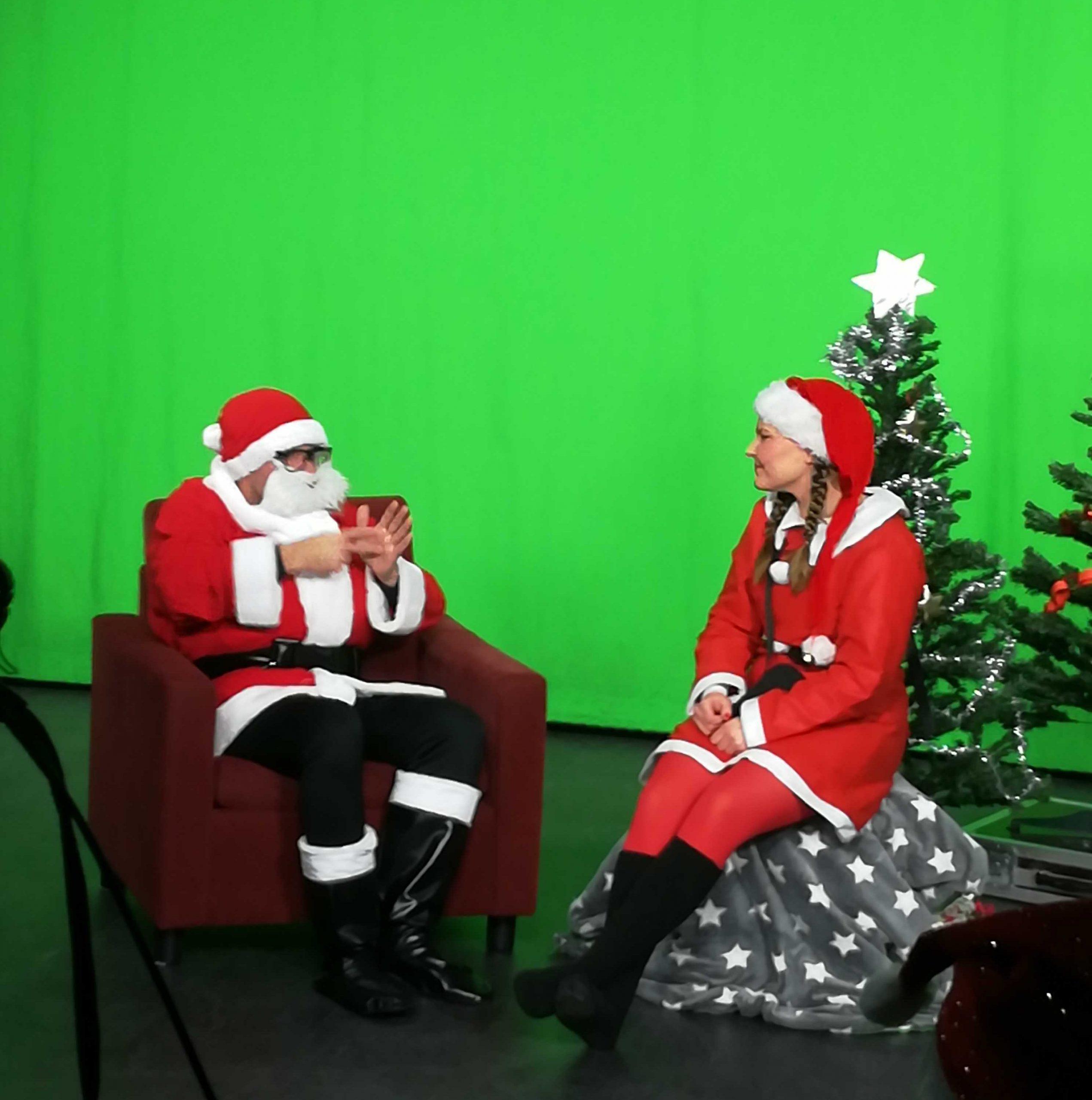 Kuvassa vihreän kankaan edessä istuvat joulupukki ja tonttuasuun sonnustautunut tyttö. Pukki viittoo tontulle