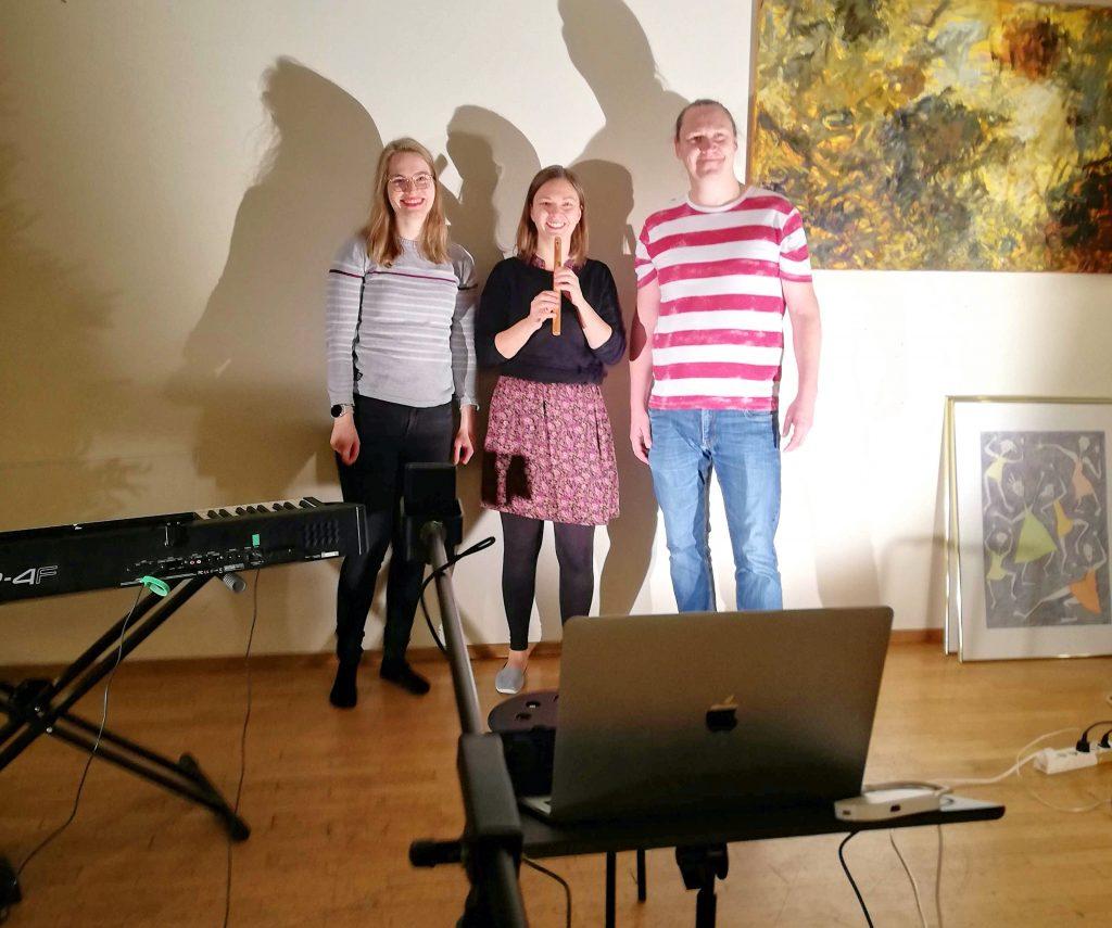 Kuvassa CIsumusan syksyn ohjaajat Reea, Salla ja Juha-matti seisomassa seinän edessä, kasvot valokuvaajaa kohti. Ympärillä näkyy soittimia, tietokone sekä tauluja. Sallalla kädessä huilu.