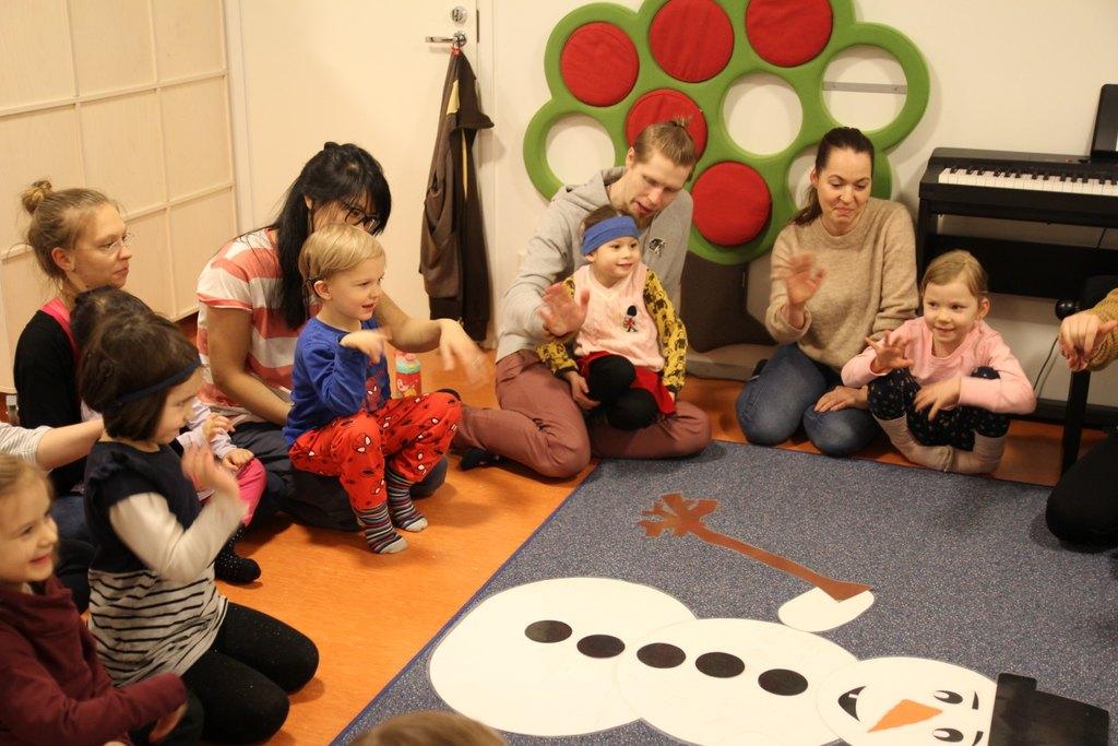 Kuvassa istuu vanhempia lattialla ympyrässä pienet lapset sylissään. Ympärillä soittimia ja lattialla lumiukko-matto