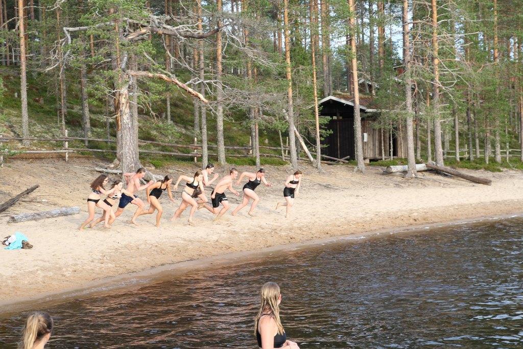 Kuvassa joukko nuoria rannalla juoksemassa kohti järveä