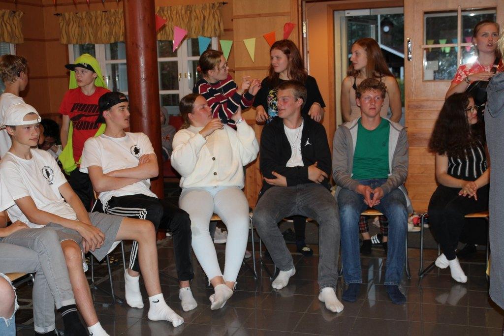 Kuvassa nuoria istuu ringissä ja juttelee toistensa kanssa