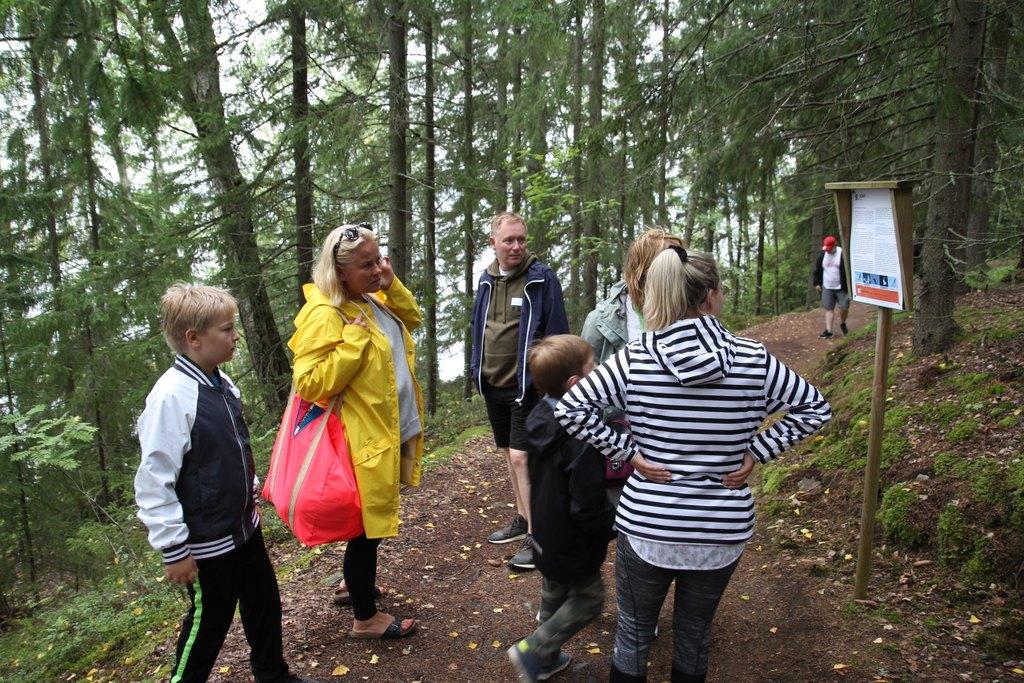 Kuvassa vanhempia ja lapsia seisomassa luontopolulla olevan infotaulun edessä