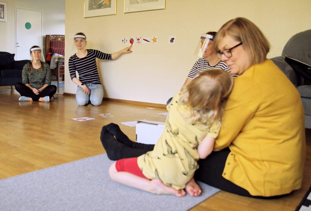 Kuvassa etualalla äiti ja lapsi lattialla istumassa. Takana näkyy CIsumusan ohjaajia osoittamassa seinällä näkyviä kuvioita