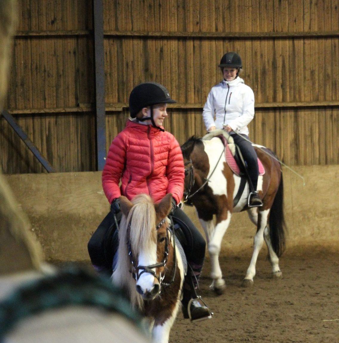 Kuvassa kaksi nuorta hevosen selässä.