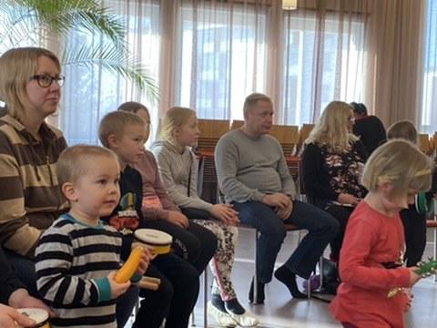 Kuvassa istuu vanhempia ja heidän edessään pieniä lapsia lelut ja soittimet käsissään
