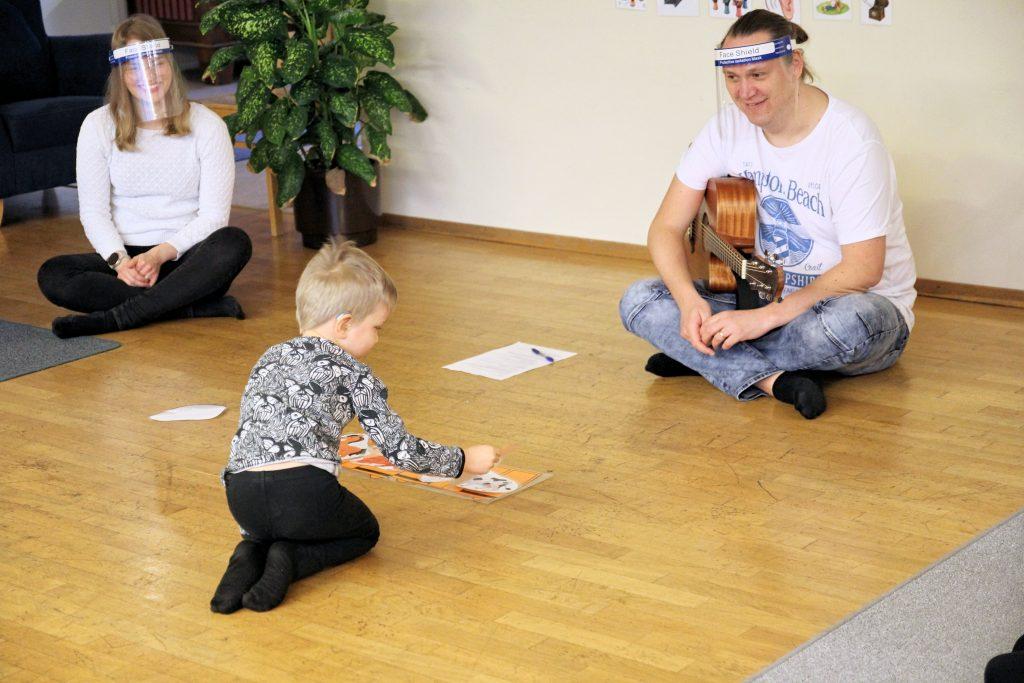 Kuvassa pieni CIsumusalainen leikkii ja taustalla kaksi ohjaajaa soittavat ja laulavat