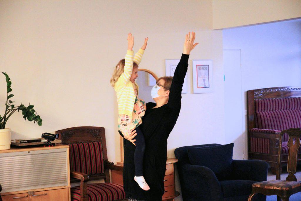 Kuvassa vanhempi pitää lasta sylissään ja he molemmat ovat nostaneet käden ylös