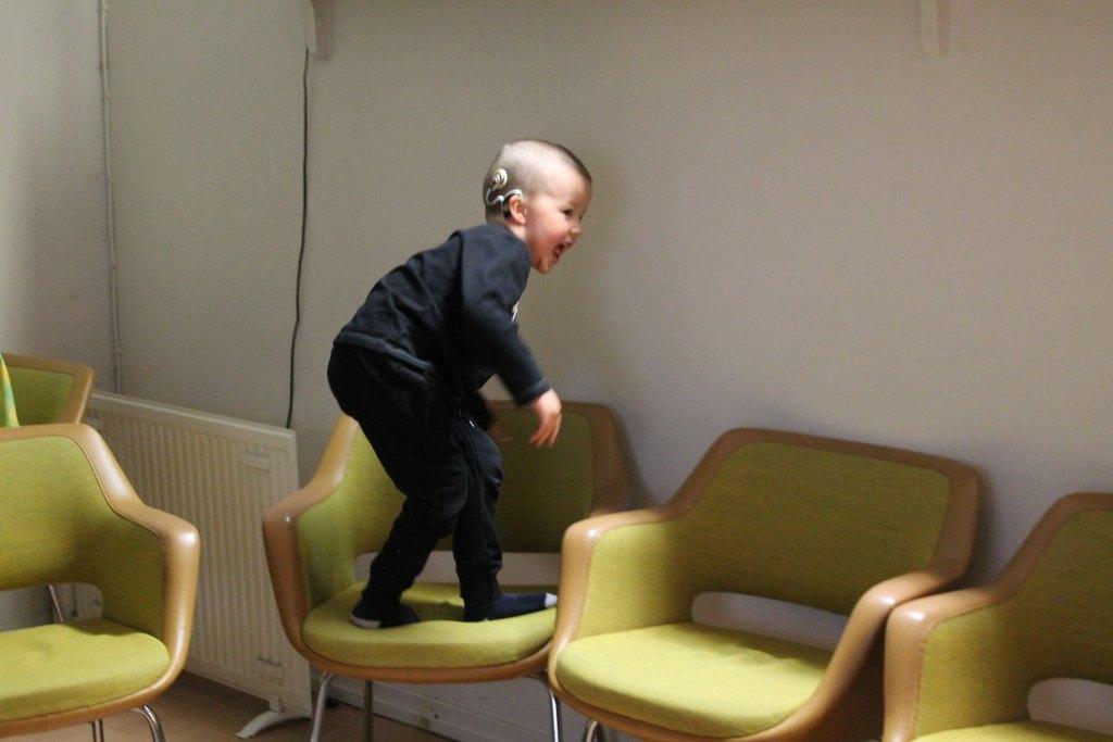 Kuvassa pieni SI:tä käyttävä poika leikkii tuolilla