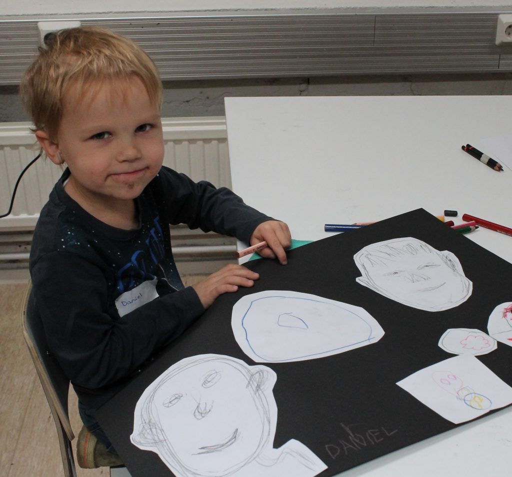Kuvassa pieni poika ja hänen vieressään pöydällä hänen tekemänsä kuvakollaasi erilaisista kasvoista