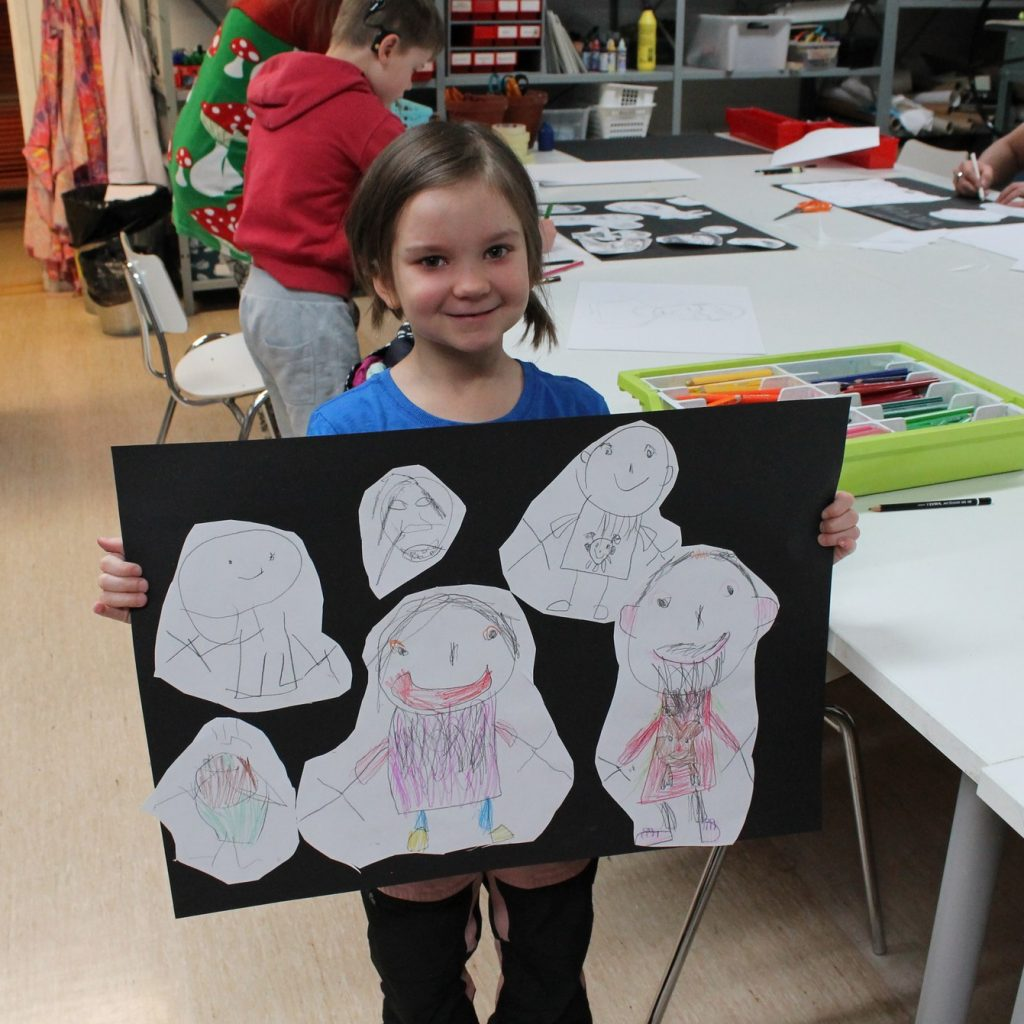 Kuvassa pieni tyttö pitää käsissään kollaasia tekemistään piirustuksista, takana näkyy muita lapsia piirtämässä pöydän ääressä.