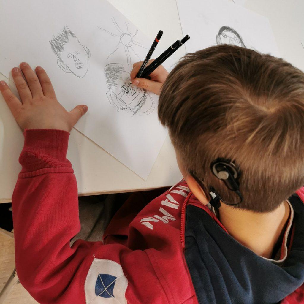 Kuva ylhäältäpäin otettu, kuvassa sisäkorvaistutetta käyttävä lapsi piirtää paperille erilaisia kasvoja