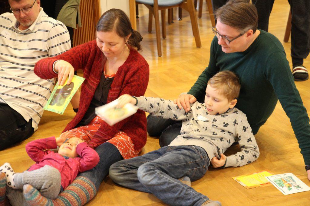 Kuvassa äiti, isä ja lapsia lattialla leikkimässä kuvakorteilla.  / teemana vuorovaikutus