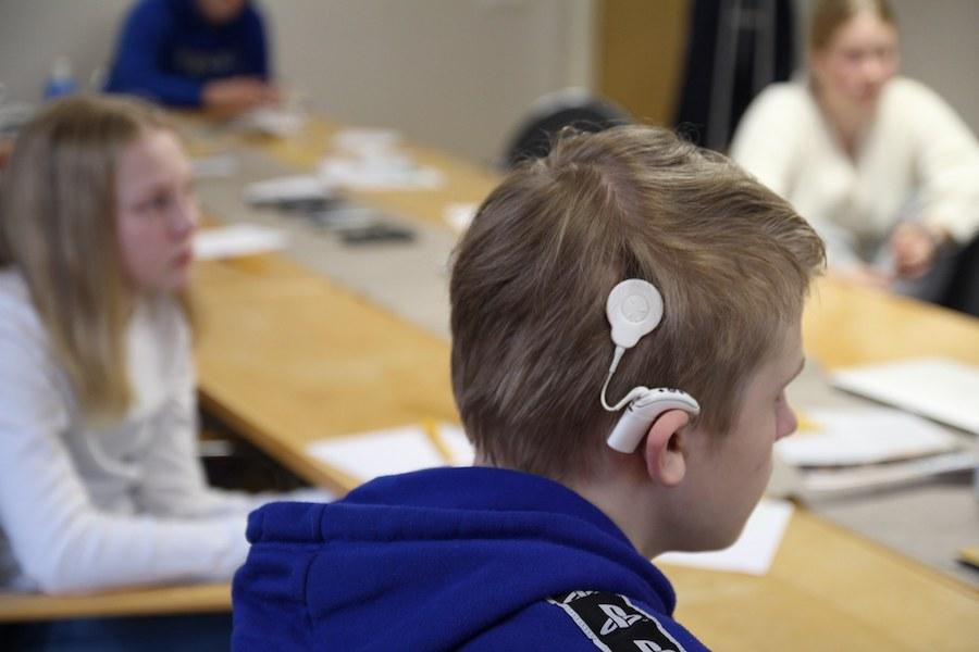 Kuvassa etualalla teini-ikäinen poika, jolla on SI. Taka-alalla näkyy muita nuoria pöydän ääressä  / SI-identiteetti