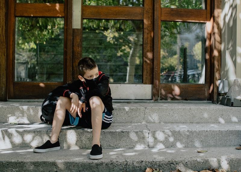 Kuvassa poika istuu koulun portailla kasvomaski päässään