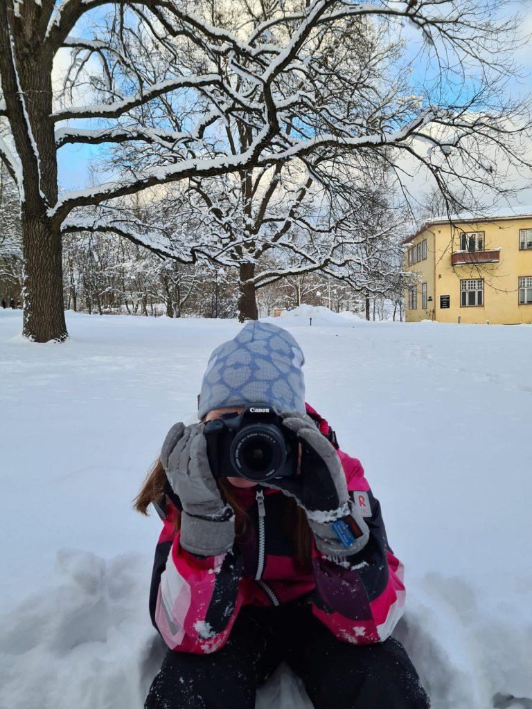 Lapsi kuvaa kameralla talvisessa maisemassa Voimauttava valokuvaus -viikonloppuna